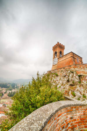 crenellated tower: crenellated clock tower above the roofs in the old town of Brisighella in the valley nestled among the hills of Emilia Romagna in Italy