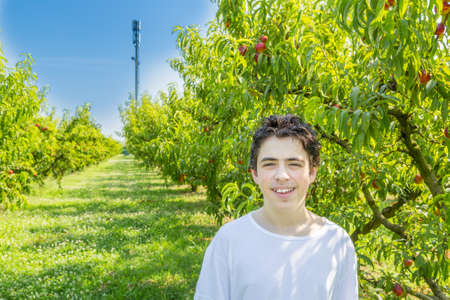repeater: teenager boy next to peach trees with Cell Phone repeater in background