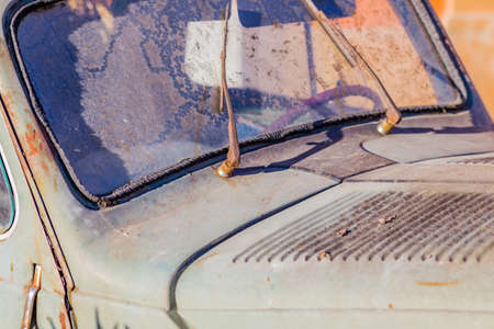 carcass: carcass of an old rusty car in the desert sand surrounded by rocks and cactus