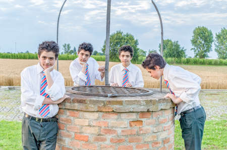 clones: Four clones of the same teenage boy look out over an old well in the countryside of Emilia Romagna