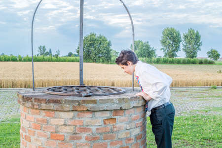 romagna: Teenage Boy looks out over an old well in the countryside of Emilia Romagna Stock Photo