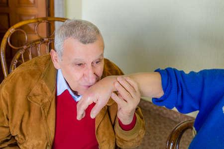 tenderly: elderly man tenderly kissing the hand of an elderly woman