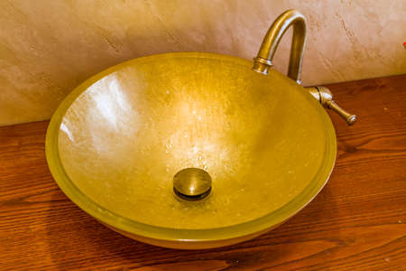 tempered: washbasin in golden leaf on tempered glass and brass faucet