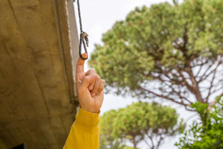 eyelet: finger pulling the eyelet of a nylon cord under a balcony in the garden