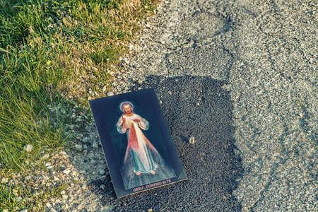 merciful: the Merciful Jesus iconon dirt asphalt road, italian sentence written on the bottom meaning Jesus I trust in You Stock Photo