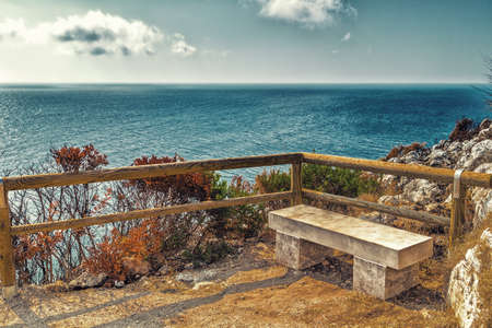steep cliffs: stone bench and wooden parapet on steep cliffs above the sea along the coast of Puglia in Italy