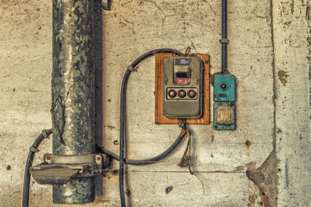 archéologie industrielle électrotechnique - ancien interrupteur de lumière électrique panneau ancien et électrique avec vannes et fusibles le long tube métallique