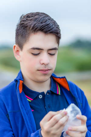 close up eyes: close up of young boy in countryside whith closed eyes while holding disposable gloves Stock Photo