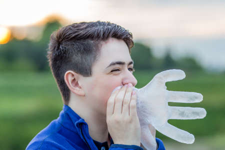 plastic glove: close up of young boy in countryside smiling while blowing in a disposable  plastic glove to inflate it