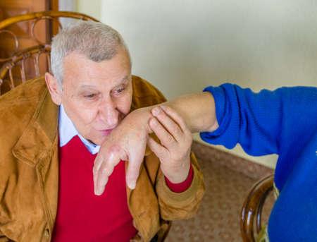tenderly: elderly man tenderly kissing the injured hand of an elderly woman