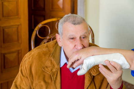 tenderly: elderly man tenderly kissing the injured hand of an elderly woman in plaster support
