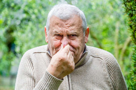 Elderly Caucasian in green garden stoppeth his nose with his fingers