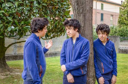 clonacion: three boys talking to each other in a garden, actually the same guy in a multiplicity photo Foto de archivo
