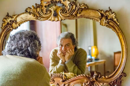 reflection: middle-aged man holds up his chin with both hands as he looks thoughtfully at his reflection in an ancient luxurious mirror