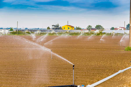 irrigating: irrigation of cultivated fields with rotating sprayers near photovoltaic panels Stock Photo
