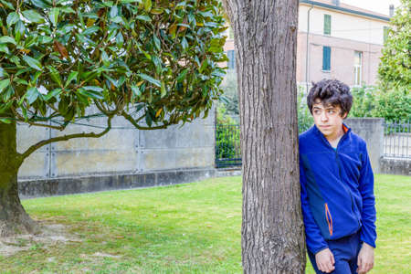 catalpa: young boy lost in thoughts  leaning against the trunk of a catalpa tree in garden Stock Photo