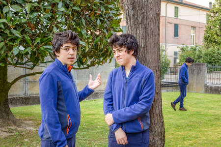 antisocial: Boys who talk to each other in a garden while another is walking alone, actually the same guy in a multiplicity photo