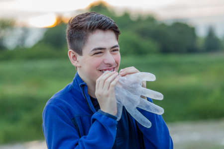 plastic glove: close up of young boy with braces in countryside laughing while going to blow in a disposable  plastic glove to inflate it
