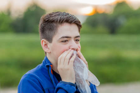plastic glove: close up of young boy in countryside blowing in a disposable  plastic glove to inflate it