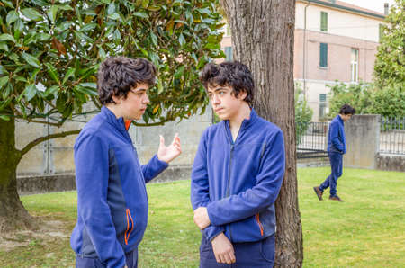 multiplicity: Boys who talk to each other in a garden while another is walking alone, actually the same guy in a multiplicity photo