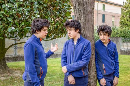 Boys who talk to each other in a garden, actually the same guy Stock Photo
