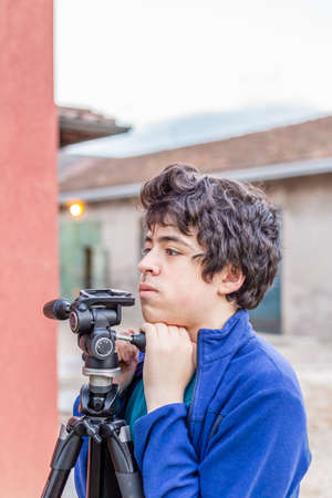 kidding: teenager kidding with a tripod in the courtyard of an old house