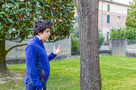 debating: young boy debating with himself in garden
