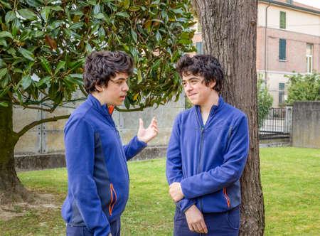 clonacion: dos niños que hablan el uno al otro en un jardín, en realidad la misma persona en una foto multiplicidad Foto de archivo