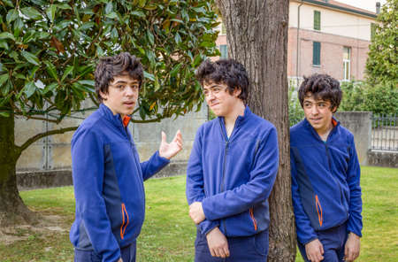 multiplicity: three boys talking to each other in a garden, actually the same guy in a multiplicity photo Stock Photo