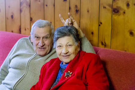 kidding: elderly couple kidding while sitting on the sofa in their living room, the man make horns sign on the head of his wife Stock Photo