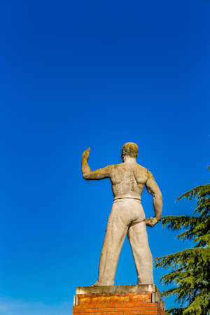raises: stocky and muscular statue of inspiration from Fascist period, a willfully man raises his left arm to the sky Stock Photo
