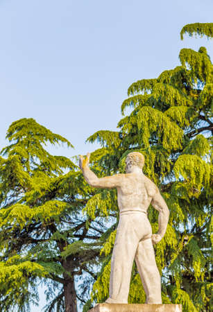fascist: stocky and muscular statue of inspiration from Fascist period, a willfully man raises his left arm to the sky Stock Photo