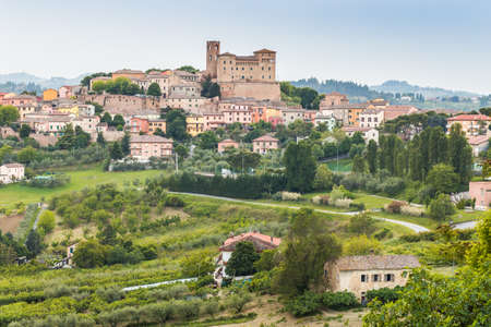 brighten: imposing castle and roofs of colored houses brighten the tranquility of a medieval village in the hills of Romagna in Italy
