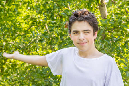 grasp: teenager next to rows of apple trees stretches out his hand to show the fields Stock Photo