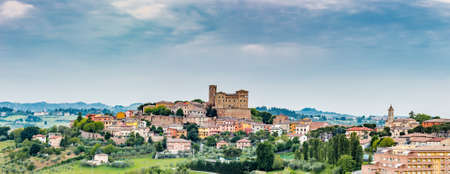 imposing: imposing castle and roofs of colored houses brighten the tranquility of a medieval village in the hills of Romagna in Italy