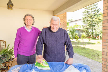 lovingly: Senior ironing in the patio of his house while another man affectionately holds his hand on his shoulder