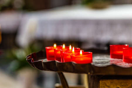 cast iron red: Red votive candles on old cast iron candlestick inside a church