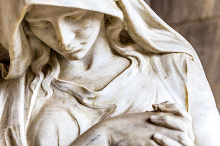 veiled: face of statue of grieving woman with her hands clasped in prayer