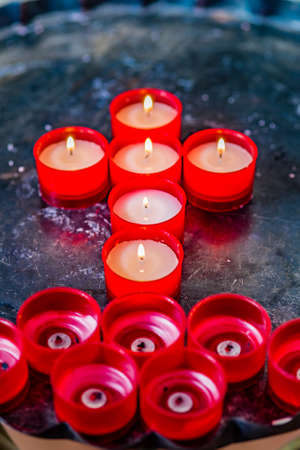 votive: votive candles form the symbol of the Cross Stock Photo
