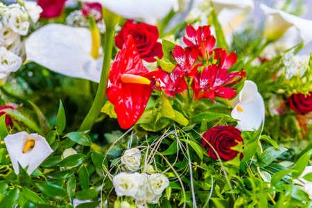 White Callas: ramo de flores rojas y blancas con hojas verdes Foto de archivo