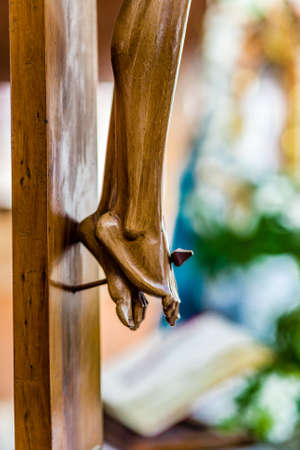 crucified: nailed feet , detail of wooden statue of Jesus Christ crucified