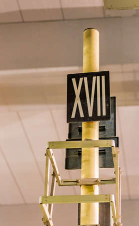 numerals: the number 17 in Roman numerals on a sign hanging from a structure
