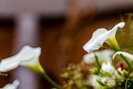 callas: Blurred wooden crucifix behind a white callas bouquet in church