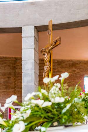 callas: wooden crucifix behind a white callas bouquet in church