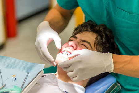 orthodontist: guy on the dentist chair while the orthodontist is checking the brackets of edgewise dental appliance