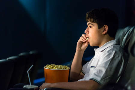 enraptured: Boy eats popcorn while watching a movie at the cinema Stock Photo