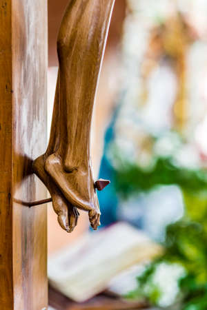 crucify: nailed feet , detail of wooden statue of Jesus Christ crucified