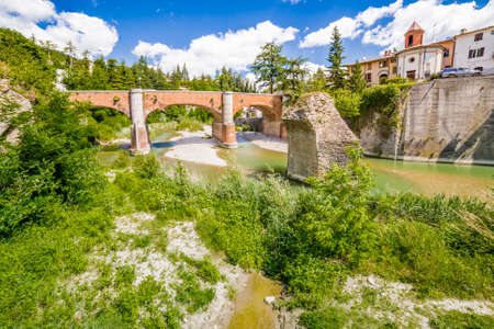 savio: waters of river running around rocky stack and under twelfth century bridge in a small village in the hills in Romagna, Italy