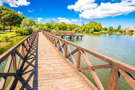 wooden boardwalk on small lake in the public park of a town in the Romagna Reklamní fotografie - 58500093