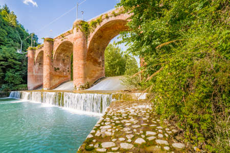 savio: Fresh waters of river running under fourteenth century bridge in masonry in a small village in the hills in Romagna, Italy Stock Photo